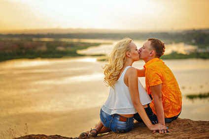 Loving couple sitting on the river bank. Kiss. Sunset. Summer day. The concept of a romantic relationship.