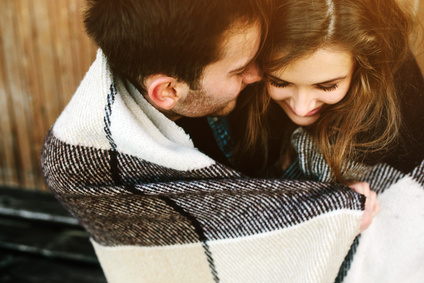 Young couple in love wrapped in plaid sitting and having fun