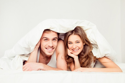 Cute young couples smiling under blanket